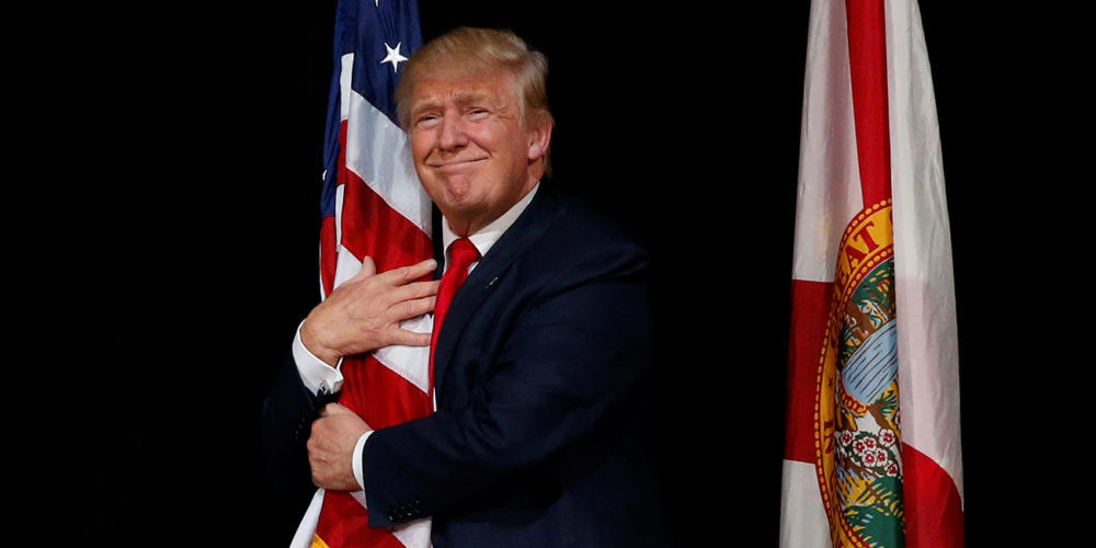 Republican U.S. presidential nominee Donald Trump hugs a U.S. flag as he comes onstage to rally with supporters in Tampa, Florida, U.S. October 24, 2016. REUTERS/Jonathan Ernst TPX IMAGES OF THE DAY - RTX2QA52